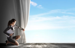 Young businesswoman opening stage curtain to another reality